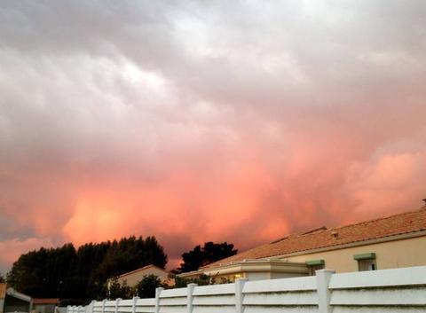 Le ciel rougeoie au-dessus des toits