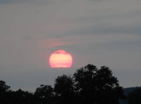 Soleil du soir en activité. Trois énormes tâches solaires sur la droites.