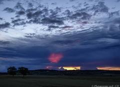 Ciel Aigueperse 63260 Une lumière rouge après l'orage.
